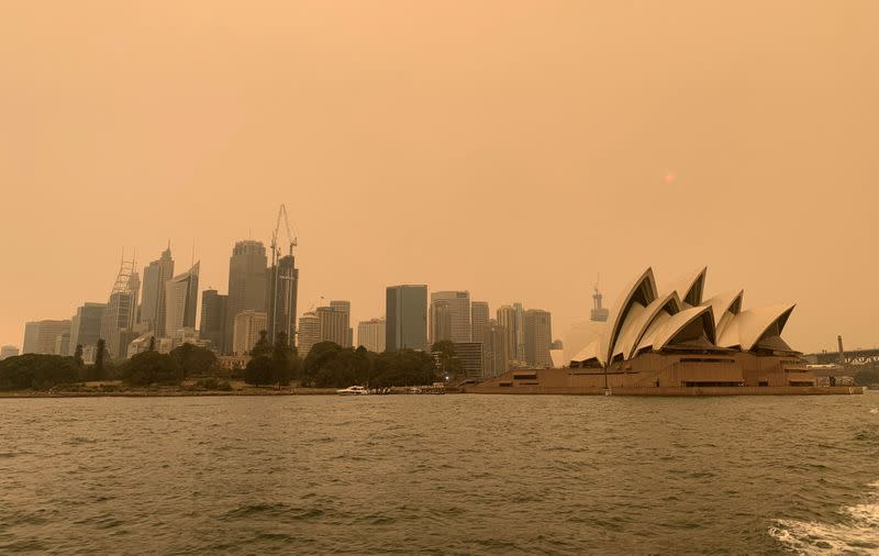 FILE PHOTO: The haze from bushfires obscures the sun setting above the Sydney Opera House in Sydney
