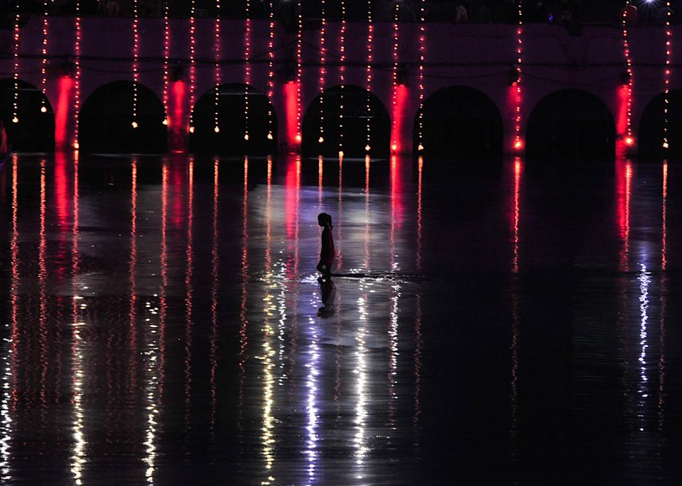 A devotee crosses Saryu river after after lighting up earthen lamps on a day before the arrival of Prime Minister Narendra Modi for Ground breaking ceremony of Ram Temple ,during the Covid 19 pandemic, in Ayodhya, India on August 4, 2020. (Photo by Ritesh Shukla/NurPhoto via Getty Images)