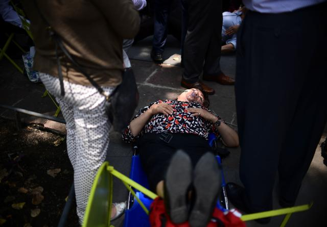<p>A woman is assisted after a real quake rattled Mexico City on September 19, 2017 while an earthquake drill was being held in the capital.<br> A powerful earthquake shook Mexico City on Tuesday, causing panic among the megalopolis' 20 million inhabitants on the 32nd anniversary of a devastating 1985 quake. The US Geological Survey put the quake's magnitude at 7.1 while Mexico's Seismological Institute said it measured 6.8 on its scale. The institute said the quake's epicenter was seven kilometers west of Chiautla de Tapia, in the neighboring state of Puebla.<br> (Photo: Ronaldo Schemidt /AFP/Getty Images) </p>