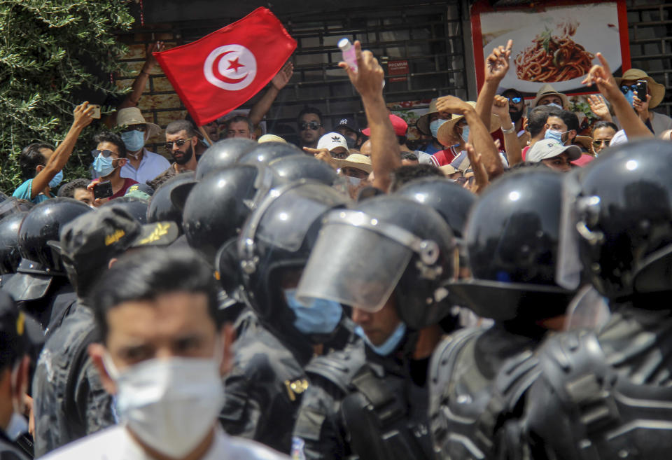 File - In this July 25, 2021 file photo, protesters face Tunisian police officers during a demonstration in Tunis, Tunisia. Days of political turmoil in Tunisia over the economy and the coronavirus have left its allies in the Middle East, Europe and the United States watching to see if the fragile democracy will survive. (AP Photo/Hassene Dridi, File)