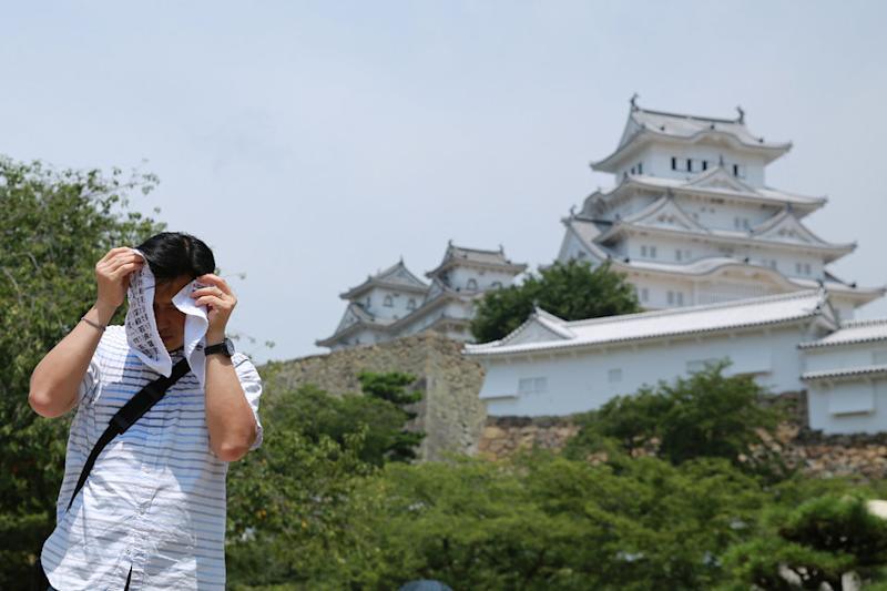 A man attempts to cover his face in Himeji, Japan.