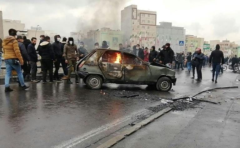 Iranians surround a burning car in the capital Tehran amid protests in the country following petrol price hikes