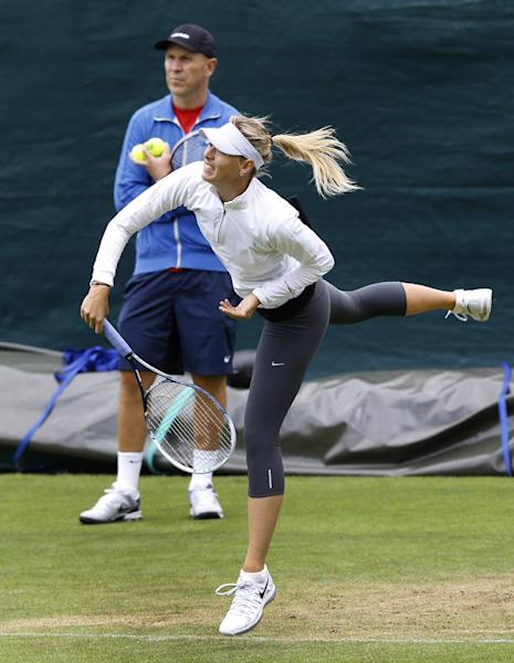 Maria Sharapova of Russia is watched by a coach during a training session at the Wimbledon tennis championships in London, Sunday, June 23, 2013. The Championships start Monday, with Serena Williams attempting to win the title for the sixth time. (AP Photo/Kirsty Wigglesworth)