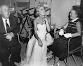 <p>Kelly chats with director Alfred Hitchcock and his wife, Alma Reville, in between takes on set in 1955.</p>