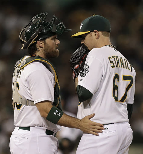 Oakland Athletics' Dan Straily, right, speaks with catcher Derek Norris in the fifth inning of a baseball game against the Los Angeles Angels Thursday, July 25, 2013, in Oakland, Calif. (AP Photo/Ben Margot)