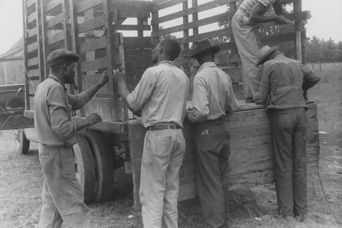 Migrant farmers prepare a truck for travel to Onley, Va., in July 1940, in a photo from the New York Public Library.
