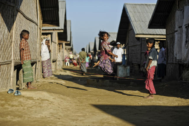 In this Nov. 30 2013 photo, Tawhera Begum, sister of Senwara, jumps as she plays with friends at the Ohn Taw refugee camp on the outskirts of Sittwe, Myanmar. Their tiny Muslim village in Myanmar's northwest Rakhine had been destroyed in a fire set by an angry Buddhist mob. (AP Photo/Kaung Htet)