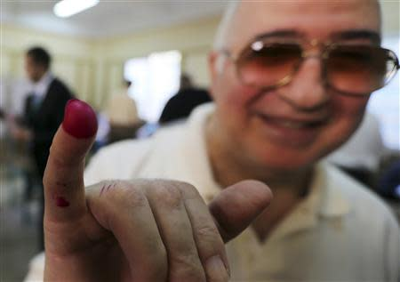 A man shows his ink-marked finger after casting his vote at a polling station during the Egyptian presidential election in Cairo