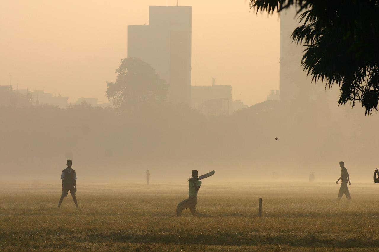 Indian boys play cricket on a foggy morning in Calcutta, India, Wednesday, Nov. 15, 2006. Environmental groups warned that India was headed for an air pollution disaster this winter and urged the government to initiate stringent pollution checks and stiff penalties to cut harmful emissions by diesel-run cars.(AP Photo/Sucheta Das)
