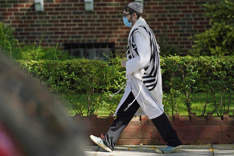 FILE - In this Sept. 28, 2020, file photo, an Orthodox Jewish man walks during Yom Kippur through the Midwood neighborhood in the Brooklyn borough of New York. Amid a new surge of COVID-19 in New York's Orthodox Jewish communities, many residents are reviving health measures that some had abandoned over the summer – social distancing, wearing masks. For many, there's also a return of anger: They feel the city is singling them out for criticism that other groups avoid. (AP Photo/Kathy Willens)