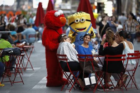 File photo of Jorge, an immigrant from Mexico, posing with women while dressed as the Sesame Street character Elmo in Times Square, New York
