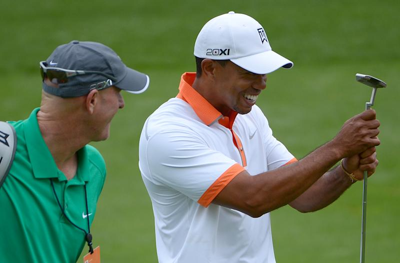 Tiger Woods, right, squeezes his putter while joking with his caddie Joe LaCava on the eighth hole during the pro-am of the Arnold Palmer Invitational golf tournament in Orlando, Fla., Wednesday, March 20, 2013.(AP Photo/Phelan M. Ebenhack)