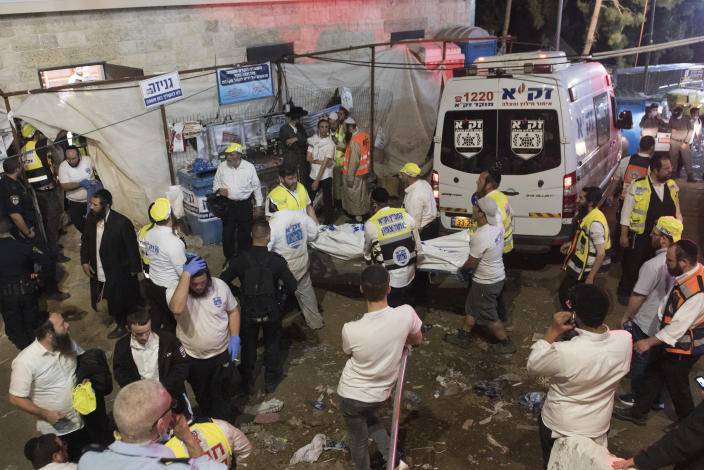 Israeli security officials and rescuers carry a body of a victim who died during a Lag Ba'Omer celebrations at Mt. Meron in northern Israel, Friday, April 30, 2021. More than 100 people were injured, dozens critically, in a stampede at a Jewish religious gathering in northern Israel attended by tens of thousands of people, Israel's main rescue service said early Friday. (AP Photo)