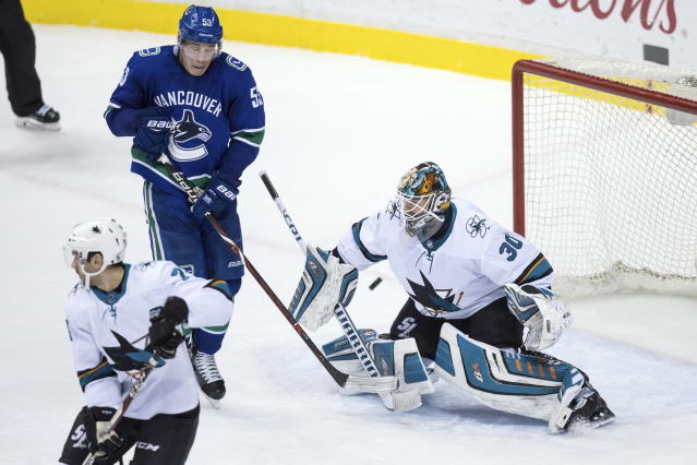 San Jose Sharks goalie Aaron Dell (30) allows a goal to Vancouver Canucks' Alexander Edler, not seen, as Canucks' Bo Horvat (53) jumps to avoid the puck during the second period of an NHL hockey game Saturday, March 17, 2018, in Vancouver, British Columbia. (Darryl Dyck/The Canadian Press via AP)