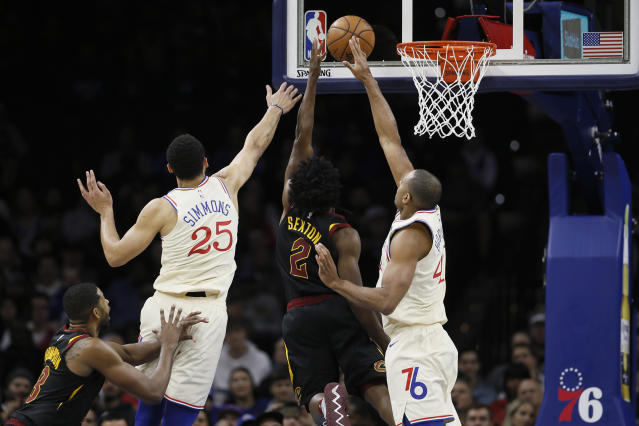 Cleveland Cavaliers' Collin Sexton (2) goes up for a shot between Philadelphia 76ers' Ben Simmons (25) and Al Horford (42) as Tristan Thompson (13) defends during the first half of an NBA basketball game, Saturday, Dec. 7, 2019, in Philadelphia. (AP Photo/Matt Slocum)