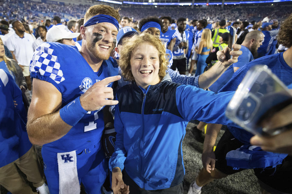 Kentucky quarterback Will Levis, left, has his photo taken with a fan on the field after winning an NCAA college football game against Florida in Lexington, Ky., Saturday, Oct. 2, 2021. (AP Photo/Michael Clubb)