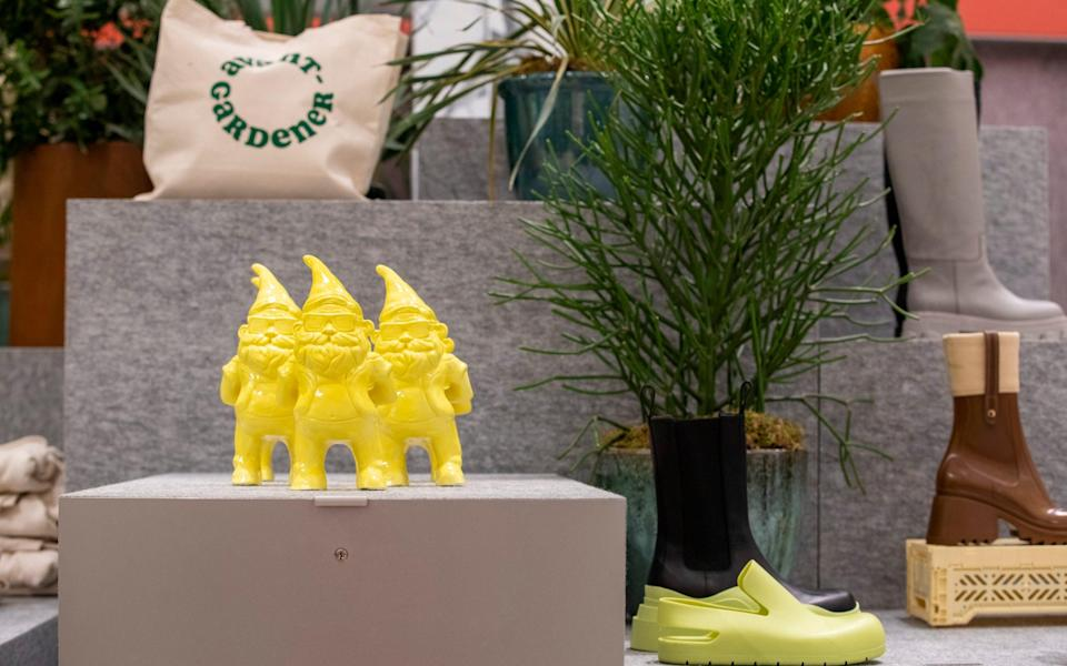 A golden trio of gnomes form part of a display at the garden centre, along with trendy printed tote bags - Rii Schroer
