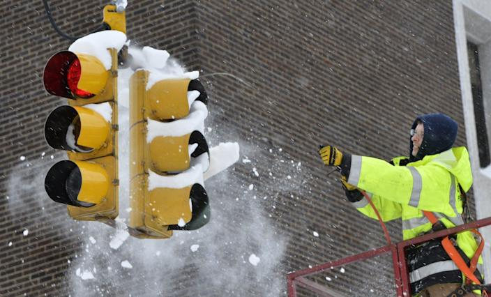 <p>City of Erie traffic engineering employee Chuck Carnes Jr. uses compressed air to clear snow from a traffic signal in Erie, Pa., Wednesday, Dec. 27, 2017. (Photo: Greg Wohlford/Erie Times-News via AP) </p>
