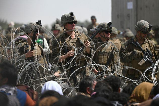 TOPSHOT - US soldiers stand guard behind barbed wire as Afghans sit on a roadside near the military part of the airport in Kabul on August 20, 2021, hoping to flee from the country after the Taliban's military takeover of Afghanistan. (Photo by Wakil KOHSAR / AFP) (Photo: xxx via AFP)