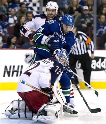 Vancouver Canucks' Chris Higgins (20) tries to get a shot past Columbus Blue Jackets goalie Sergei Bobrovsky (72) as Blue Jackets defenseman Fedor Tyutin (51) watches during the first period of an NHL hockey game in Vancouver, British Columbia, Tuesday, March 26, 2013. (AP Photo/The Canadian Press, Jonathan Hayward)
