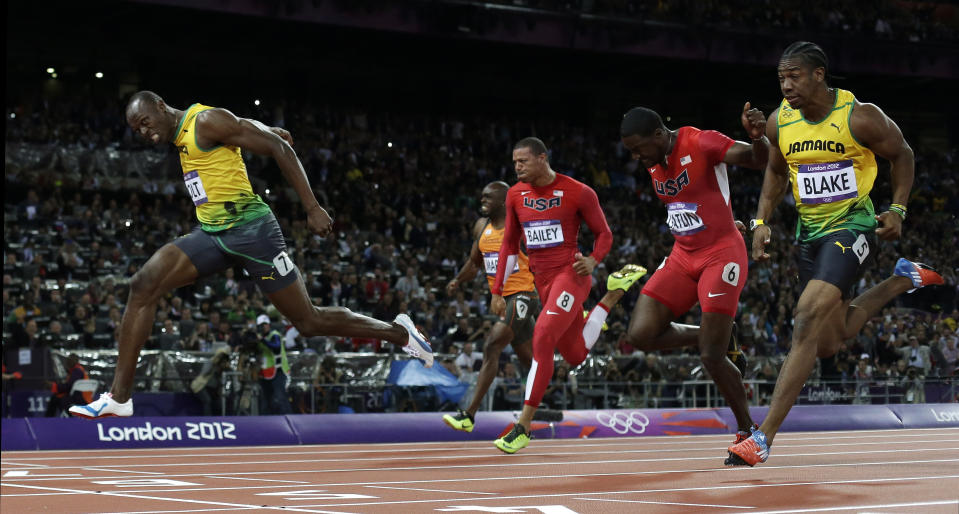 Jamaica's Usain Bolt, left, crosses the finish line ahead of Jamaica's Yohan Blake, right, United States' Justin Gatlin, second from right, United State's Ryan Bailey, third from right, and Netherlands' Churandy Martina to win gold in the men's 100-meter final during the athletics in the Olympic Stadium at the 2012 Summer Olympics, London, Sunday, Aug. 5, 2012. (AP Photo/David J. Phillip )