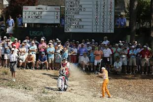 Rickie Fowler hits from the natural area on the fourth hole. (AP)