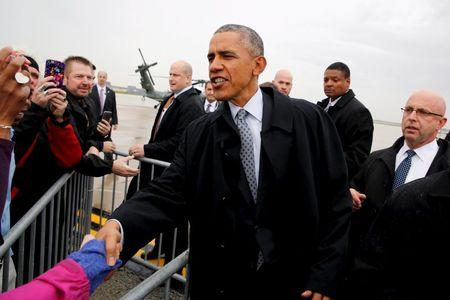 U.S. President Barack Obama greets people as he arrives at O'Hare International Airport in Chicago