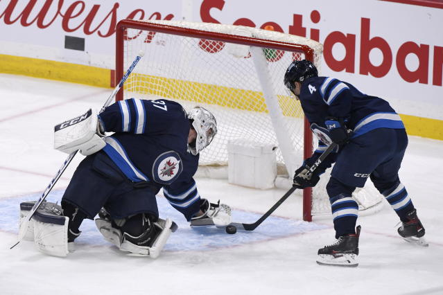 Winnipeg Jets' goaltender Connor Hellebuyck (37) and Neal Pionk (4) stop the puck from crossing the goal line after an Edmonton Oilers shot during the first period of an NHL hockey game in Winnipeg, Manitoba, Sunday, Oct. 20, 2019. (Fred Greenslade/The Canadian Press via AP)