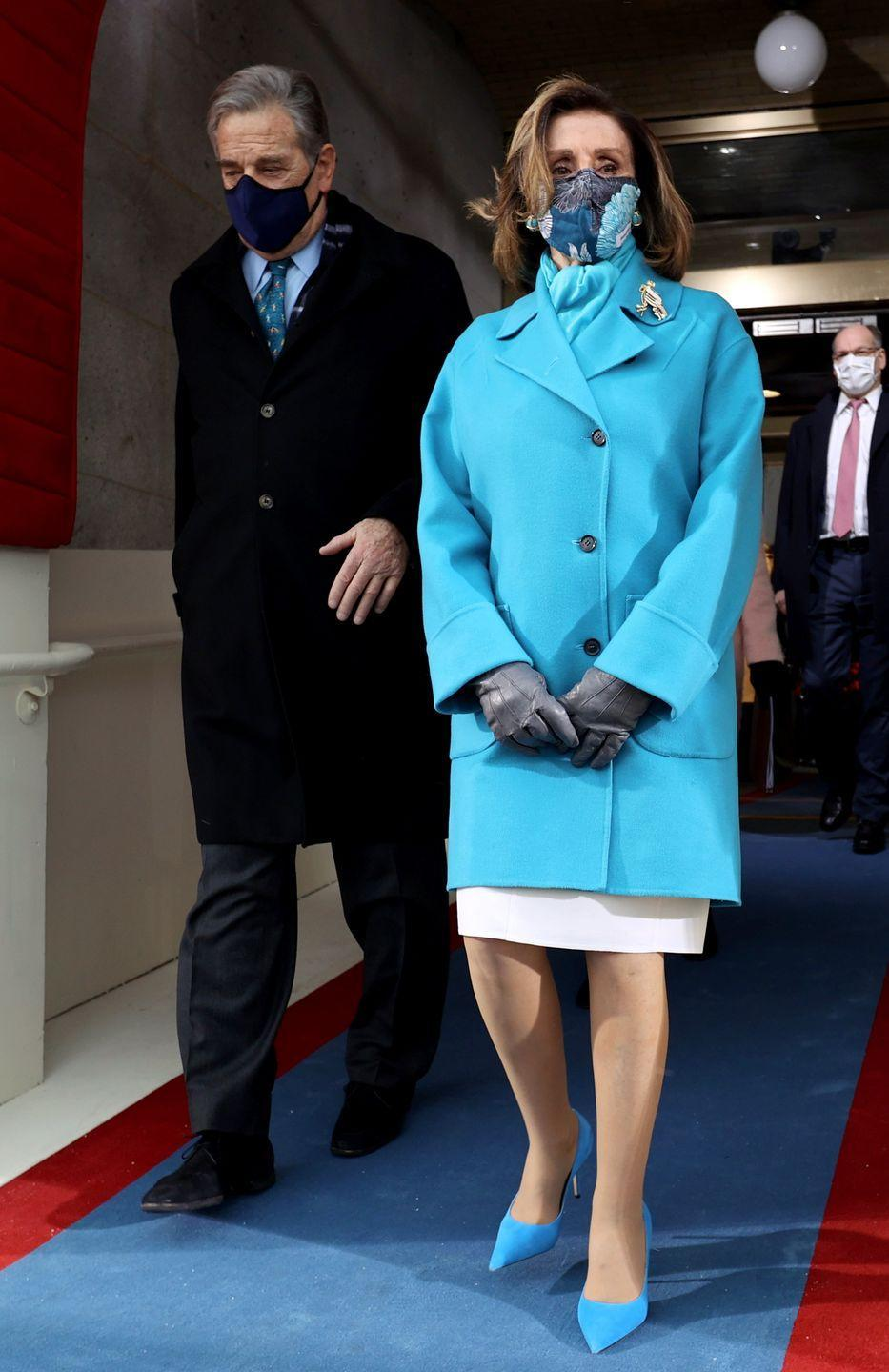 <p>Nancy Pelosi, the Speaker of the House, followed the monochromatic theme of the day and chose a cheerful shade of turquoise for her coat, scarf, and matching heels for the ceremony. Leather gloves, a well-placed brooch, and patterned mask complete the look. </p>