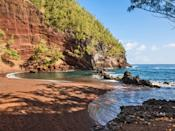 """Tucked at the base of a lava cinder cone that gives the sand its signature rust-red color, Kaihalulu, again in <a href=""""https://www.cntraveler.com/activities/maui/road-to-hana?mbid=synd_yahoo_rss"""" rel=""""nofollow noopener"""" target=""""_blank"""" data-ylk=""""slk:Hana"""" class=""""link rapid-noclick-resp"""">Hana</a>, is a photographer's dream. Its calm, protected waters are a surreal shade of Kool-Aid blue and are perfect for both swimming and snorkeling (just steer clear of the cliff-jumpers at either end of the cove). Be warned: the hike down is steep and narrow—don't attempt it when it's rainy!—but the views alone make it worth the slightly gnarly trek."""