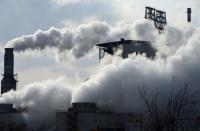 FILE PHOTO: Smoke rises from chimneys at a Sinopec refinery in Qingdao, Shangdong province