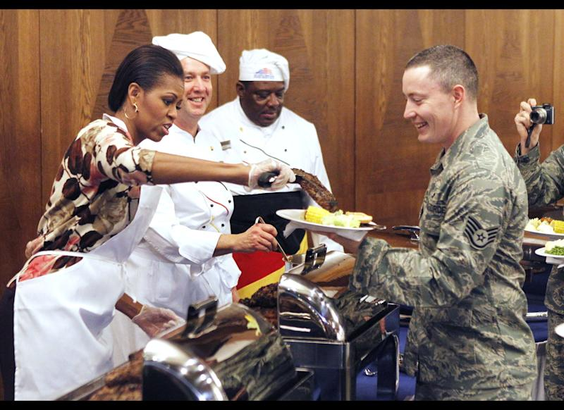 The first lady of the United States Michelle Obama, left, serves food for US soldiers and their relatives at Ramstein Airbase in Ramstein, Germany, Thursday, Nov. 11, 2010. Michelle Obama makes a series of stops within the Kaiserslautern Military Community on Veterans Day to thank US servicemen and women for their work. (AP Photo/Michael Probst)