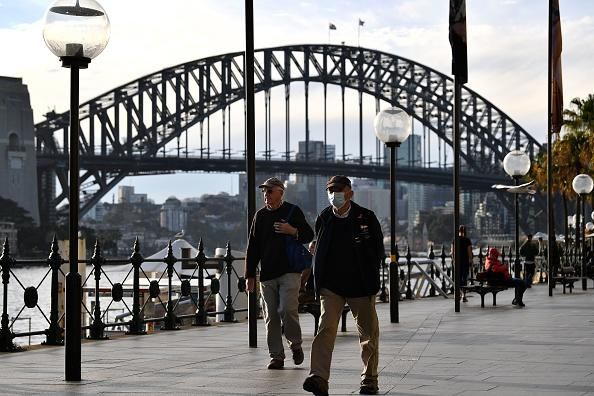 A man wearing a face mask walks before the Harbour Bridge in Sydney.