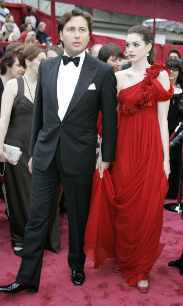 "In this Feb. 24, 2008 file photo, actress Anne Hathaway, right, walks the red carpet with her then-boyfriend Raffaello Follieri, at the Kodak Theater for the 80th Academy Awards in Los Angeles. Follieri was released Friday morning from a prison in Loretto, 80 miles east of Pittsburgh. Follieri pleaded guilty to cheating investors by falsely claiming he had Vatican connections that enabled him to buy church property at a discount. He was sentenced in 2008 to 4 1/2 years in prison. Follieri agrees he owes more than $3.6 million to those he ripped off. The proceeds supported a playboy lifestyle that included a $37,000-a-month New York City apartment and lavish vacations with the star of ""The Princess Diaries."" (AP Photo/Amy Sancetta, file)"