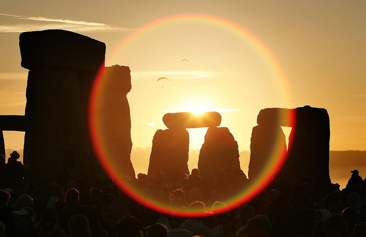 WILTSHIRE, UNITED KINGDOM - JUNE 21:  People watch the midsummer sun as it rises over the megalithic monument of Stonehenge on June 21, 2005 on Salisbury Plain, England. Crowds gathered at the ancient stone circle to celebrate the Summer Solstice; the longest day of the year in the Northern Hemisphere.  (Photo by Peter Macdiarmid/Getty Images)