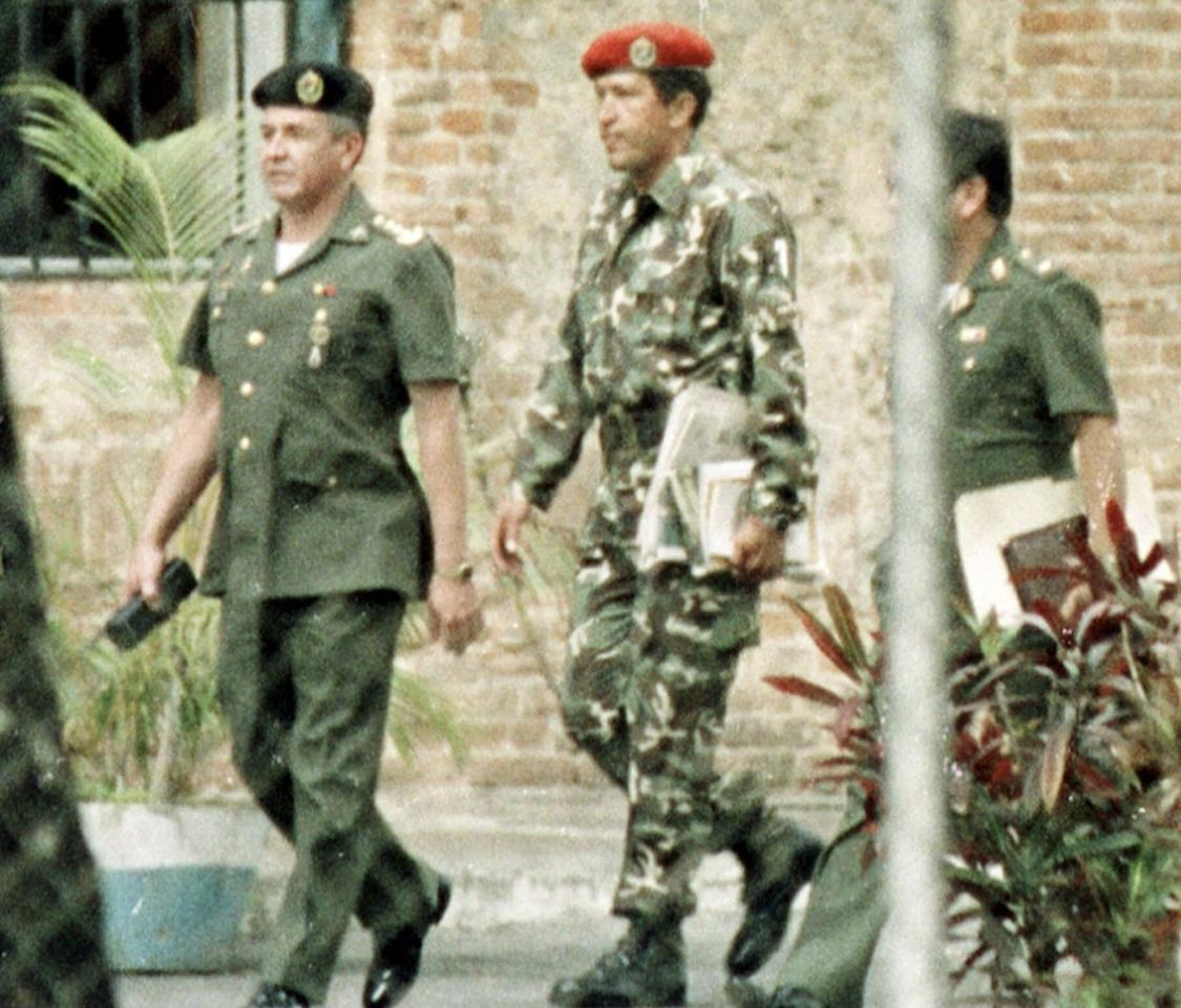 ŽFILE - In this Feb. 5, 1992 file photo, paratroop commander Hugo Chavez, center, is escorted by military intelligence officers after being arrested for trying to overthrow Venezuela's government in a coup. Venezuela's Vice President Nicolas Maduro announced on Tuesday, March 5, 2013 that Chavez has died. Chavez, 58, was first diagnosed with cancer in June 2011. (AP Photo/Andres Leighton, File)