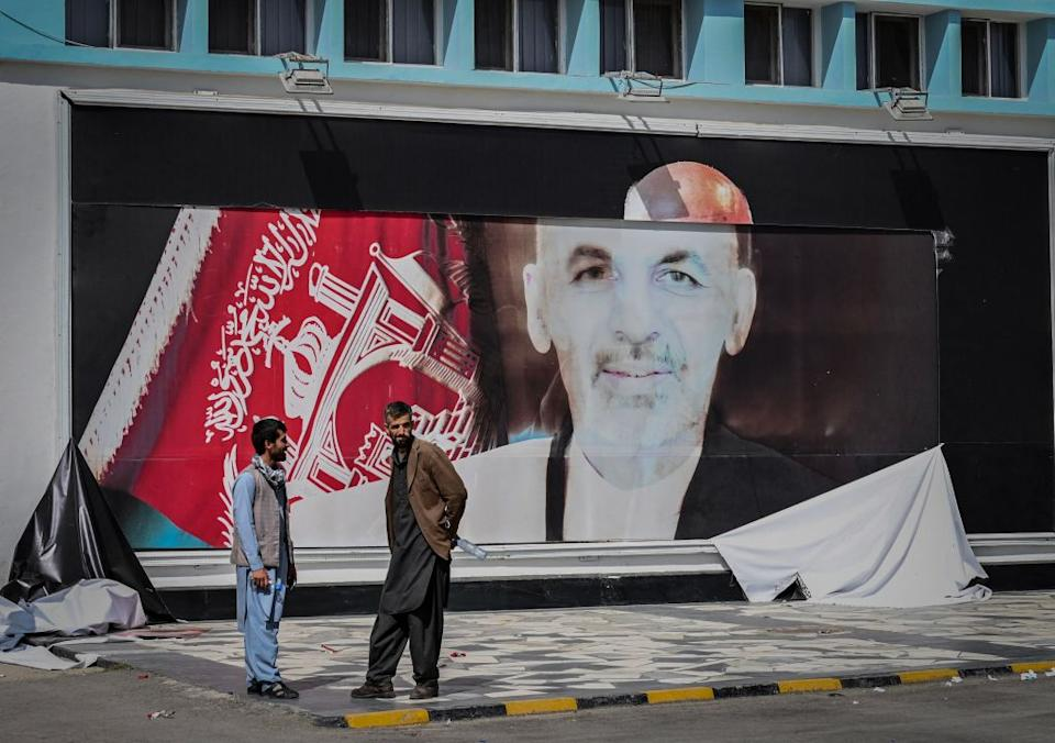 Afghan men stand next to the a torn poster of Afghan President Ashraf Ghani at the Kabul airport in Kabul.