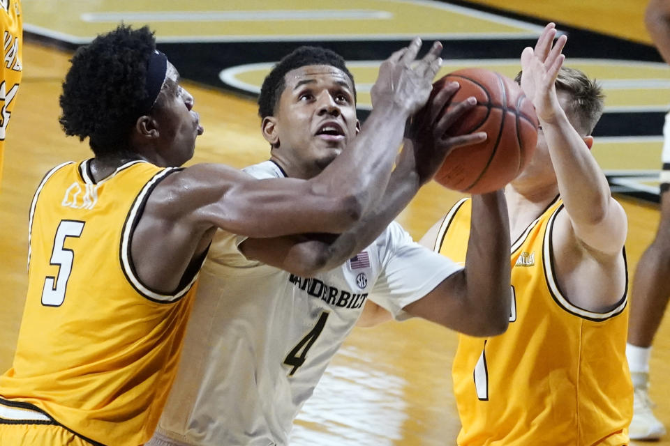 Vanderbilt guard Jordan Wright (4) tries to shoot between Valparaiso guards Donovan Clay (5) and Sigurd Lorange (1) in the first half of an NCAA college basketball game Friday, Nov. 27, 2020, in Nashville, Tenn. (AP Photo/Mark Humphrey)