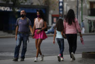 Sex worker Geraldine, 30, holds hands with her partner Miguel as she arrives outside the Revolution subway station to wait for clients, in Mexico City, Sunday, March 14, 2021. Miguel, who has been told to stay home from his job at a call center since his diabetes puts him at high risk for coronavirus complications, now spends his days accompanying Geraldine to work, exchanging jokes and the occasional kiss as he sits nearby, giving her snacks during the long hours of waiting, and keeping an eye on clients to help her stay safe in an area with high levels of crime and drug use. (AP Photo/Rebecca Blackwell)
