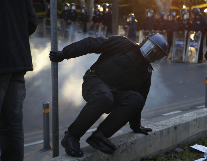 A riot police runs after a firework explodes, thrown by a protestor outside of the Parliament during a strike to protest government plans to privatize the state-run organization in Nicosia, Cyprus, Thursday, Feb. 27, 2014. Hundreds of protesters have gathered outside Cyprus' parliament to voice opposition against legislation that will pave the way for the privatization of state-owned companies. (AP Photo/Petros Karadjias)