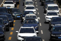A motorist cuts into center lane as motorists clogged with heavy traffic on a city ring road in Beijing, Tuesday, Aug. 11, 2020. China's auto sales rose by 16.4% in July over a year earlier to 2.1 million units in a sign of sustained recovery for the industry's biggest global market, an industry group said Tuesday. (AP Photo/Andy Wong)