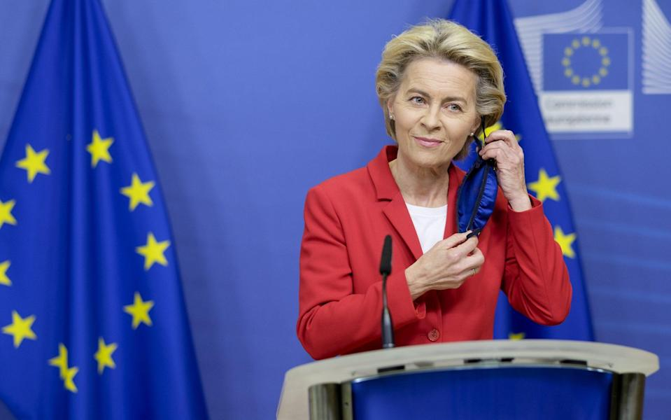 European Commission President Ursula von der Leyen takes off her mask before speaking to the media in the Berlaymont, the EU Commission headquarter on October 1, 2020, in Brussels