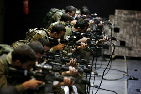 Israeli soldiers respond with laser-firing rifles to a simulated Palestinian attack playing out on an interactive screen, during an open-fire scenario training in Camp Tsur infantry training base in southern Israel