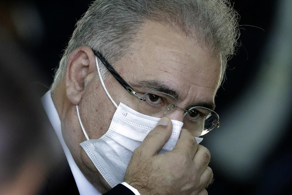 FILE - In this March 24, 2021 file photo, Brazil's new Health Minister Marcelo Queiroga adjusts his protective face mask before the start of a press conference, at the presidential residence Alvorada Palace in Brasilia, Brazil. Queiroga, the fourth man to occupy the health ministry post during the COVID-19 pandemic, is a doctor who speaks about the need to boost vaccine supply, consults with scientists and has so far displayed the autonomy to promote mask use and social distancing. (AP Photo/Eraldo Peres, File)
