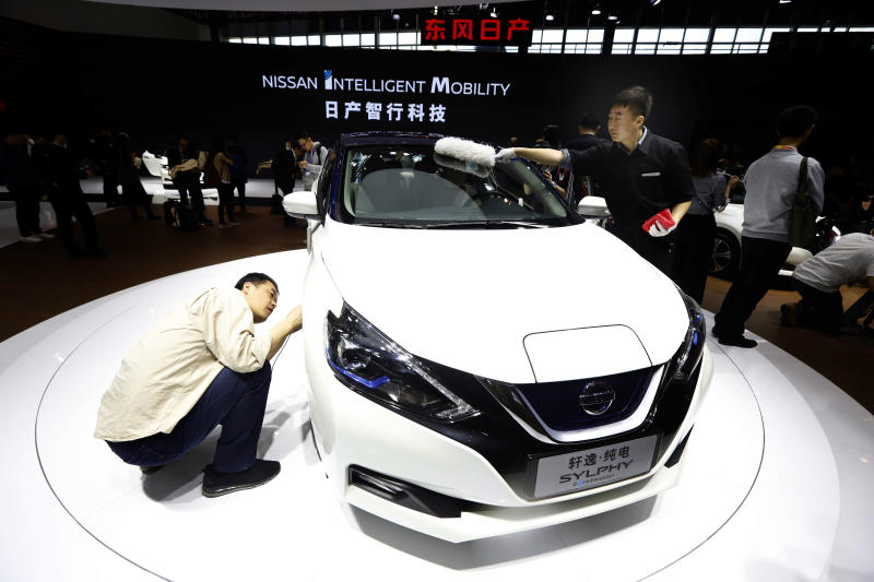 FILE - In this April 25, 2018, file photo, a visitor takes a closer look at the Sylphy Zero Emission during the start of the Auto China 2018 in Beijing, China. The 2019 Shanghai auto show highlights the global industry's race to transform electric cars into a profitable product Chinese drivers want to buy as Beijing winds down multibillion-dollar subsidies that made this country the biggest market for the technology. (AP Photo/Ng Han Guan, File)