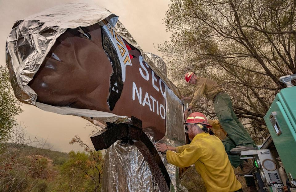 Firefighters wrap the iconic entrance sign at Sequoia National Park in California with a fire-resistant blanket on Tuesday. The sign, restored in recent years, has stood since 1935.