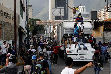 Demonstrators stand on a truck while clashing with riot security forces during a rally against Venezuela's President Nicolas Maduro in Caracas, Venezuela, May 31, 2017. REUTERS/Carlos Garcia Rawlins
