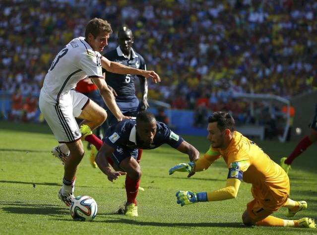 France's goalkeeper Hugo Lloris (R) makes a save past his teammate Patrice Evra and Germany's Thomas Mueller (L) during the 2014 World Cup quarter-finals soccer match at the Maracana stadium in Rio de Janeiro July 4, 2014. REUTERS/Pilar Olivares (BRAZIL - Tags: SOCCER SPORT WORLD CUP)