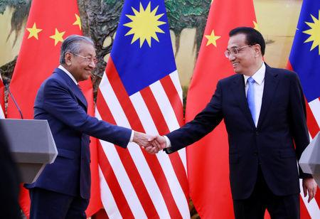 Malaysia's Prime Minister Mahathir Mohamad (L) shakes hands with China's Premier Li Keqiang at the end of a news conference at the Great Hall of the People in Beijing, China, August, 20, 2018. How Hwee Young/Pool via REUTERS