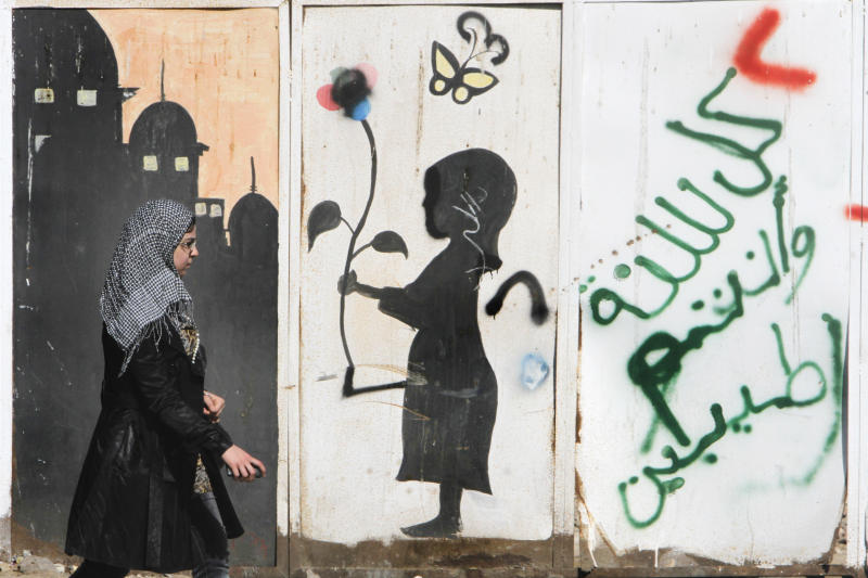"""An Egyptian walks in front of graffiti in the upscale neighborhood of Zamalek, Cairo, Egypt, Saturday, March 23, 2013. Egypt has faced near-constant turmoil in the more than two years since longtime, authoritarian leader Hosni Mubarak was overthrown in a revolt. The unrest has badly hurt the economy, with foreign investors and tourists largely staying away, and a diesel crisis that has crippled life for millions. Arabic reads, """"happy new year."""" (AP Photo/Amr Nabil)"""